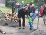 Köhler Gerd Schramm zeigt dem jüngsten Besucher den Kohlenmeiler